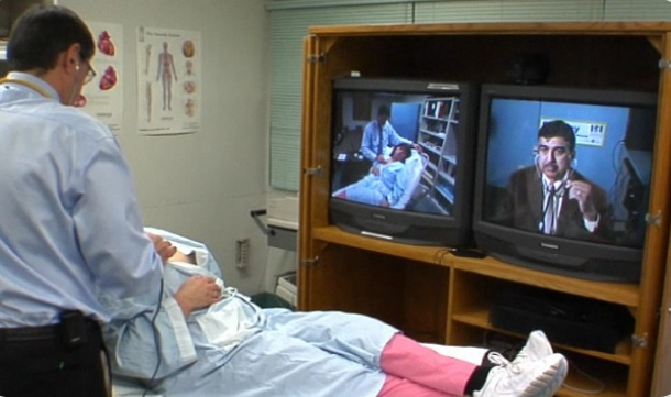 "A patient and doctor in an OTN telemedicine ""studio"" conference with a specialist at another hospital. All of Ontario's hospitals have at least one telemedicine studio."