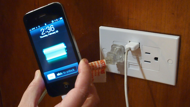 Success! Here, the Power2U is powering a small lamp while charging an iPhone.