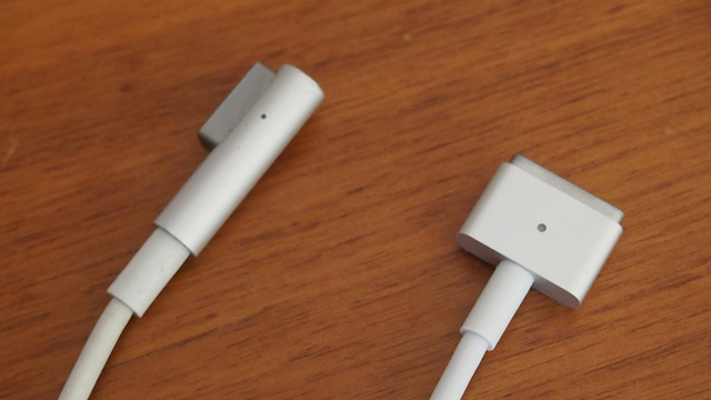 "The MagSafe connector (left) compared to the new MagSafe2 connector (right). The new design looks similar to the original ""T"" style MagSafe connectors, but it is sheathed in brushed metal with sturdy reinforcement where the cable meets the connector."