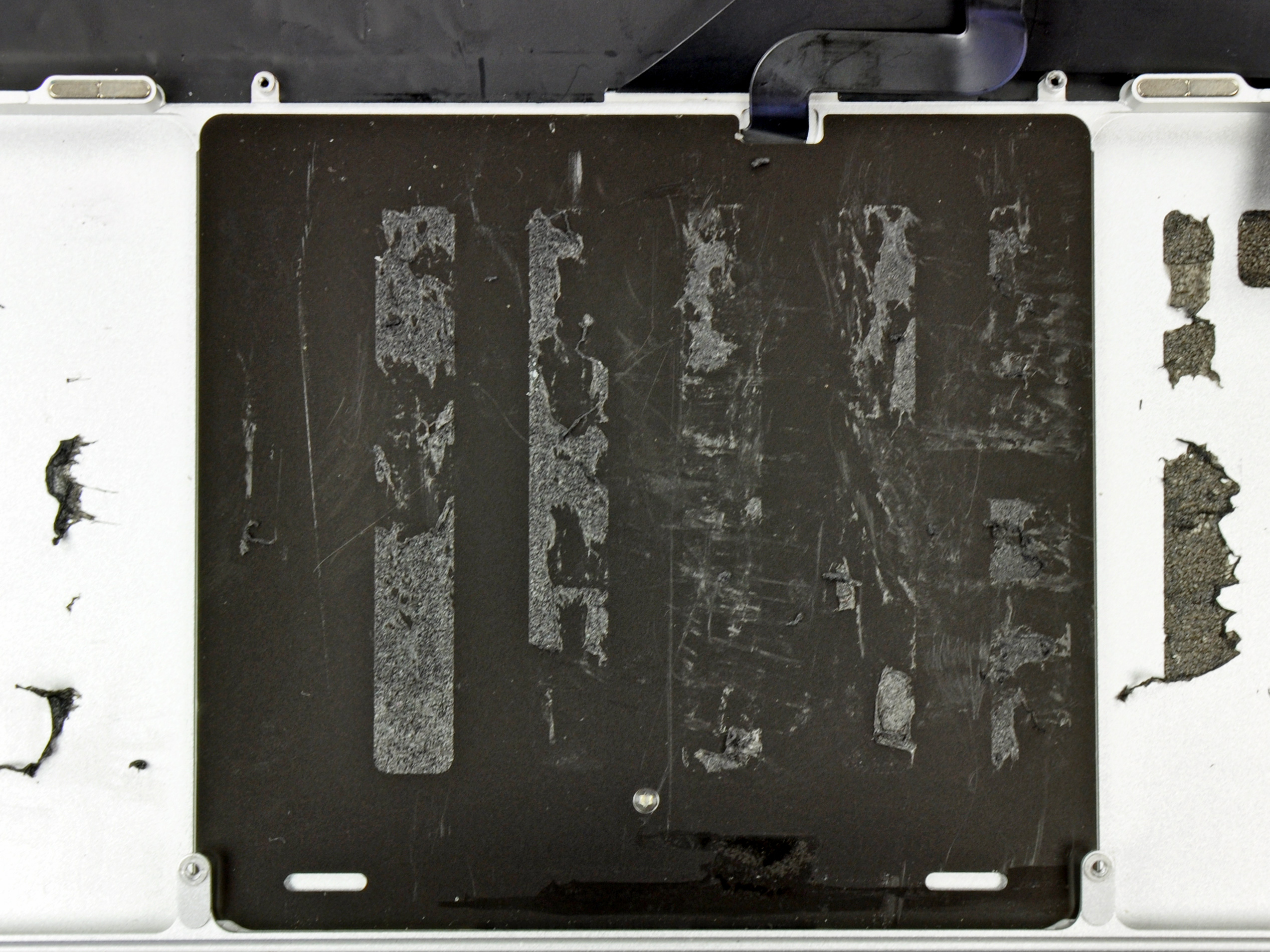 To the left and right of the underside of the trackpad, you can just discern the edges of the sculpted wells that hold four of the Retina MacBook Pro's six Li-Po cells.