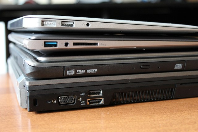 The UX31A, second from the top of the stack, compared to the MacBook Air (top of the stack), the Acer Aspire Timeline Ultra M5 gaming Ultrabook (second from bottom), and my chunky old Dell Latitude E6410 (bottom).