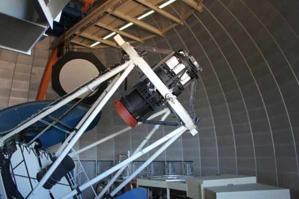 DECam on the Victor M. Blanco telescope. The camera itself is the black cylinder at the image center. Light from distant galaxies is focused by the 4-meter-diameter mirror at left into the camera.