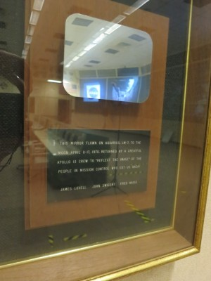 This plaque, featuring one of the mirrors from Apollo 13's Lunar Module <em>Aquarius</em>, hangs on the wall in MOCR 2 today.