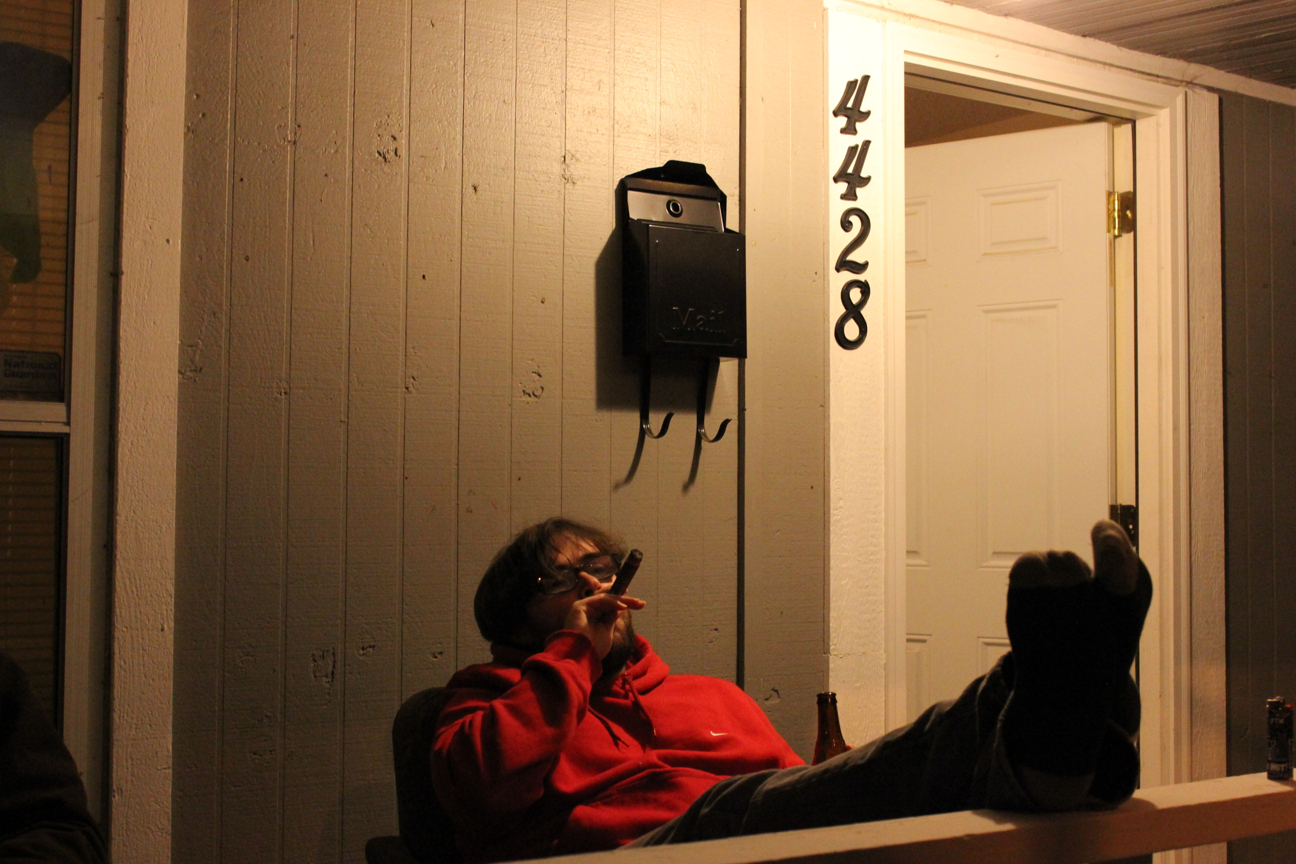 Andrew Evans relaxes Wednesday evening with a cigar on the porch of the Hacker Home.