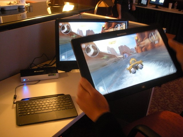 Wilocity's Teresa Liou plays a game on a tablet, which is mirrored onto the monitor through the docking station on the left.