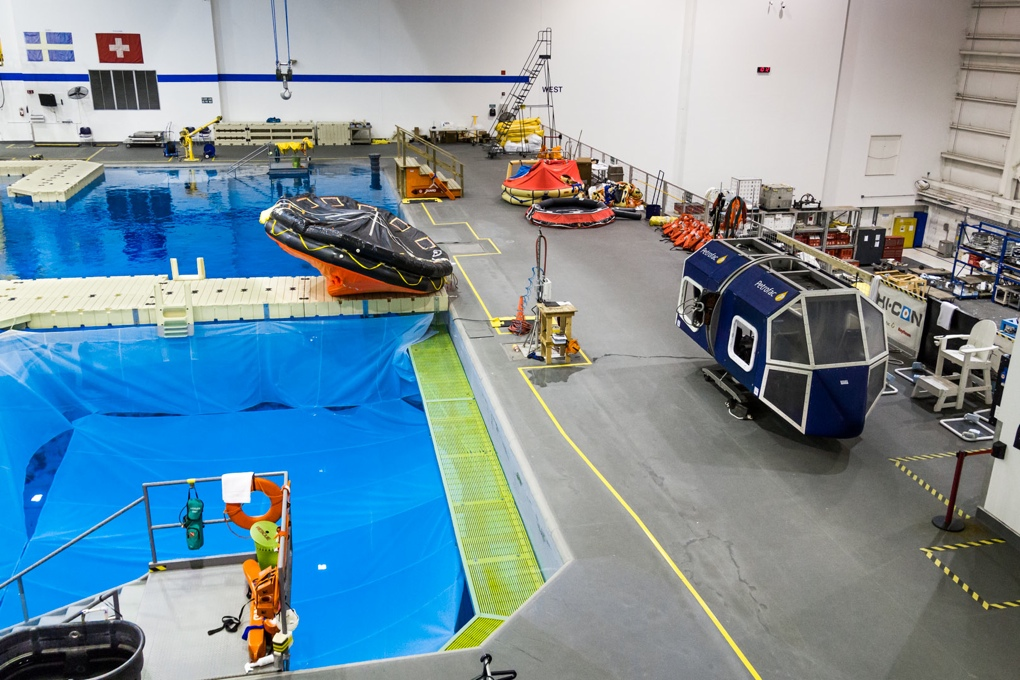One end of the NBL is roped off for use by commercial programs. At right is the blue helicopter cabin mock-up used for emergency egress training.