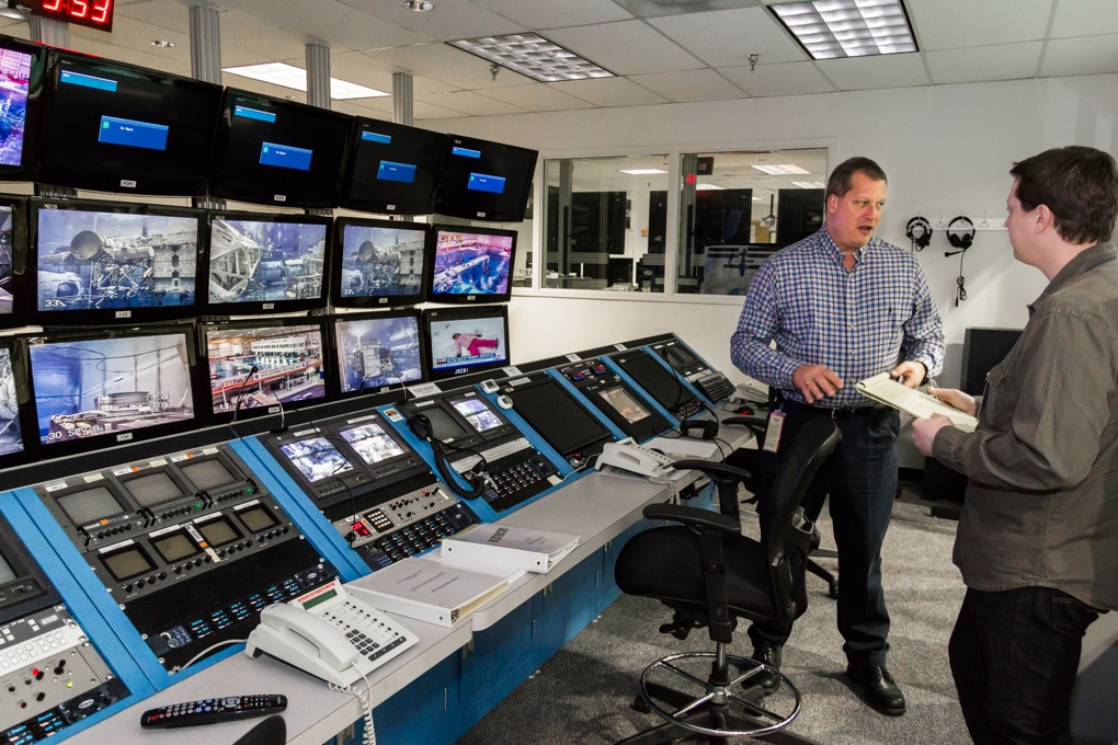 Kurt Otten stands in front of the test director console, explaining how the NBL runs.