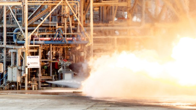 The gas generator firing. Visible emerging from the nozzle is the dark, fuel-rich exhaust, which takes a bit of time to completely burn. This is characteristic of gas generator exhausts.