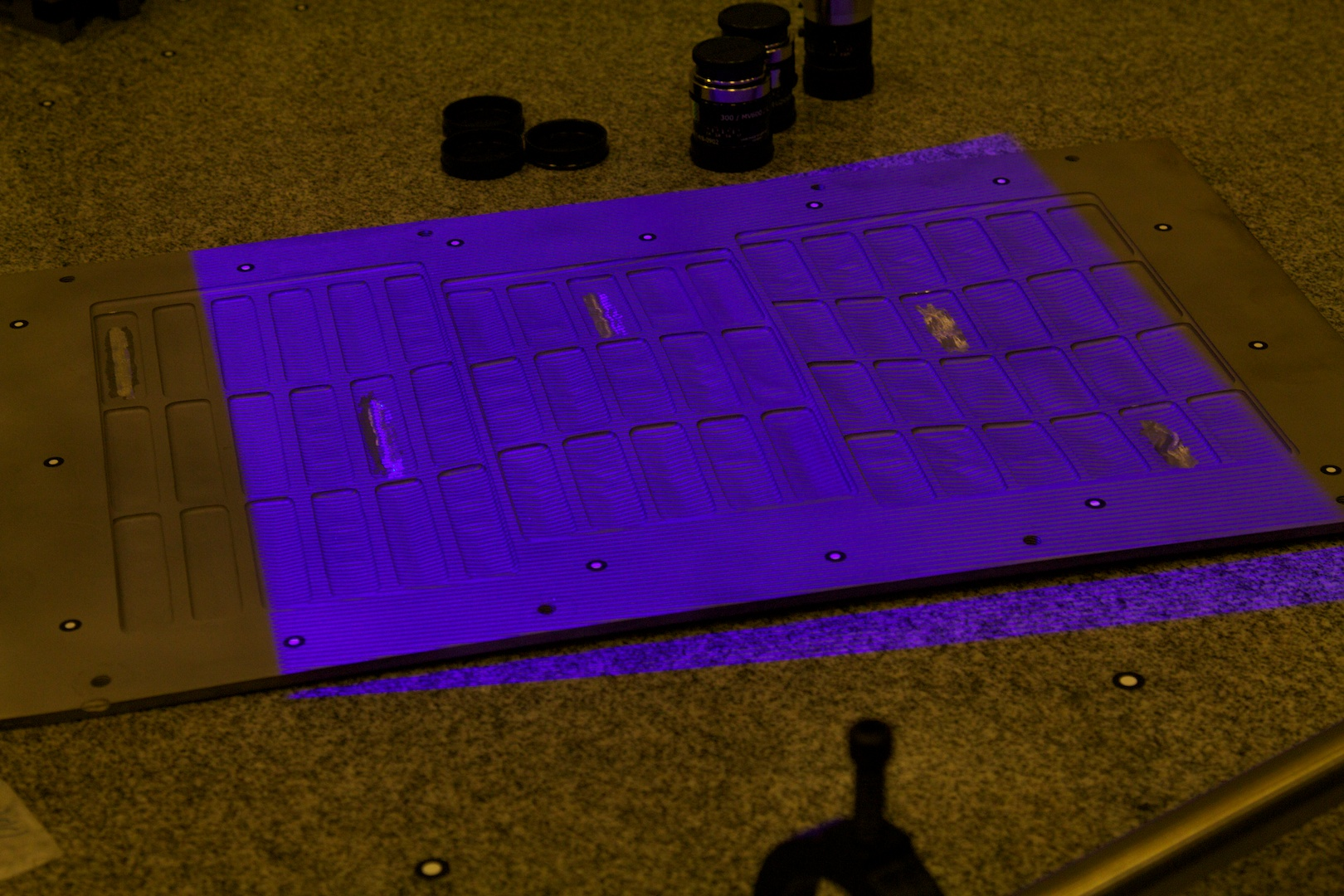 Scanning a small object with the structured light scanner. The alternating horizontal bars in the purple projection are used by the cameras to detect surface detail. Note positional decals around the object's perimeter.