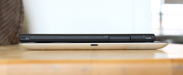 The Tablet 2 stacked on top of a fourth-generation iPad. The tablet has a micro USB port for charging on its left side, as well as a full-size USB 2.0 port for accessories. The full-size USB port is hidden under a small flap.