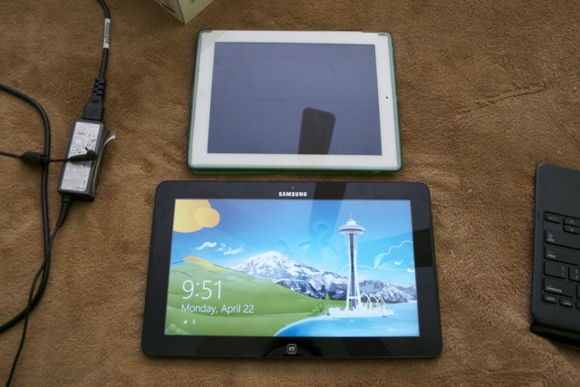 A size comparison between the Ativ Tab 7 in tablet mode (alongside its power supply) and an iPad 2.