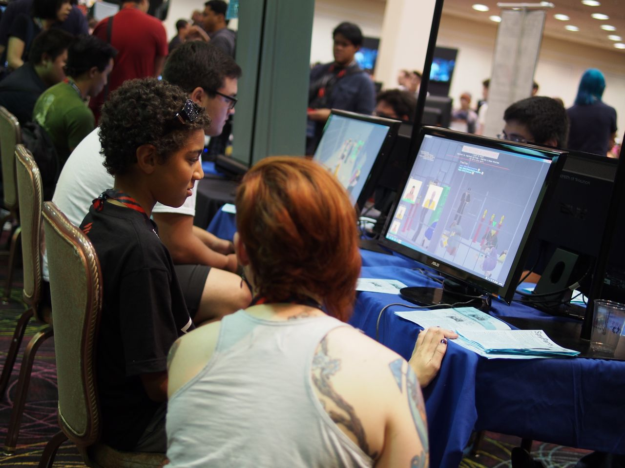 An attendee gets a personal lesson in how to play <i>Spy Party</i> at the Evo indie game showcase.