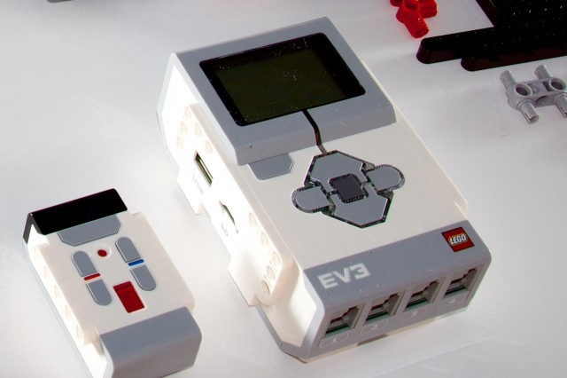 "At right, the programmable EV3 ""intelligent brick,"" which houses the microprocessor and which drives the motors and sensors. At left, the small multi-channel infrared remote control."