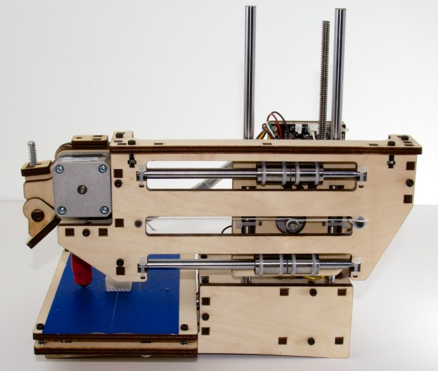 The back of the Printrbot Simple, showing guide rods and motor. Visible right of center is the pulley and string used to move the print arm back and forth.