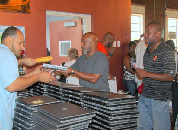 "At Digit All Systems' ""Stop Shooting, Start Coding"" event on July 15, a member of DAS' staff distributes laptops to people who have turned in firearms to police."
