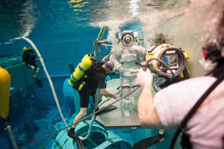 """Divers have """"rescued"""" me following a simulated suit failure (notice the stream of bubbles coming from my right wrist). The diver in the foreground has an underwater camera fixed on me to allow folks in the test control room to monitor the situation."""