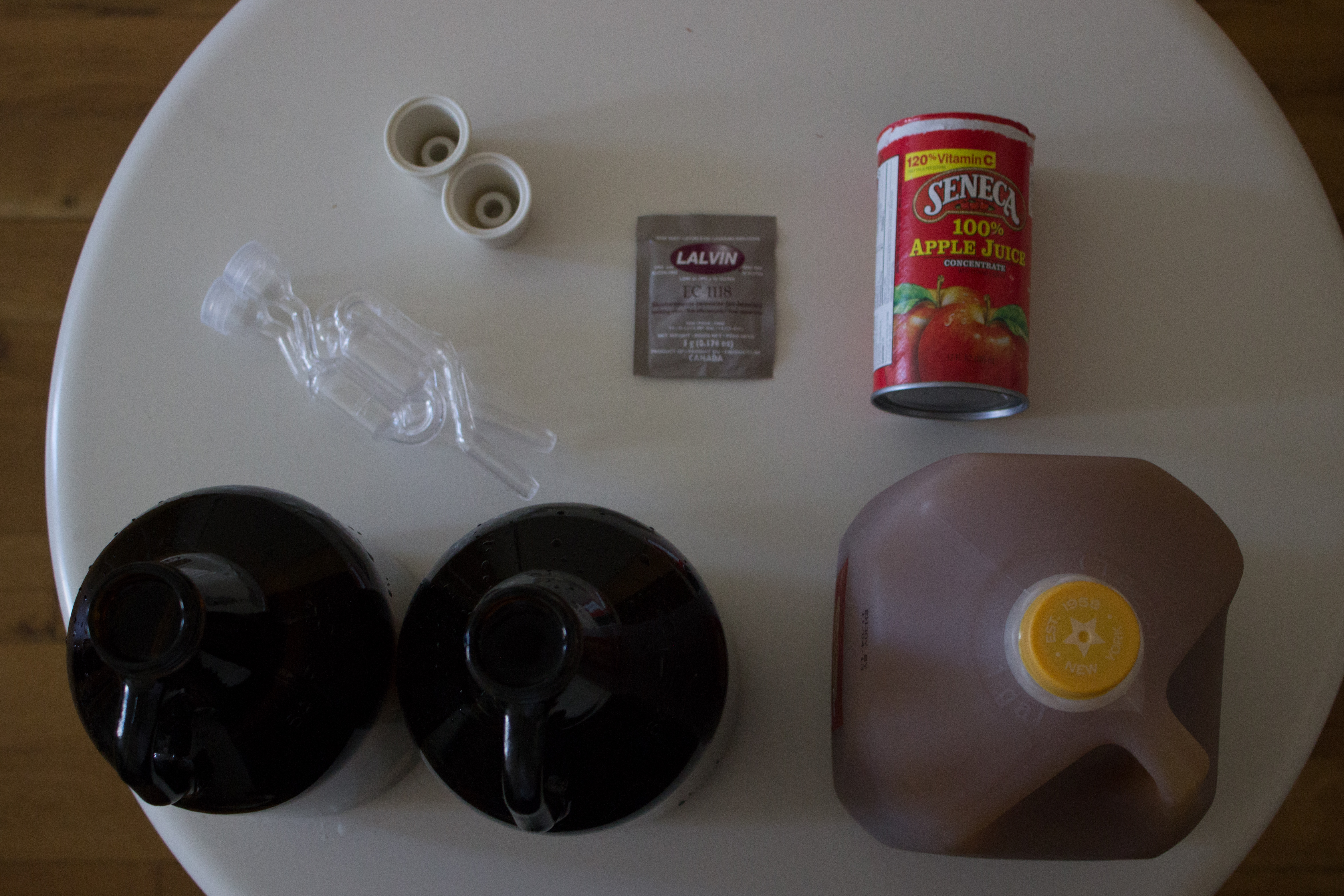 The materials of cider-making, clockwise from top left: two airlocks, two rubber bungs for stopping the fermentation vessels, a packet of yeast, apple juice concentrate, apple cider, two growlers.