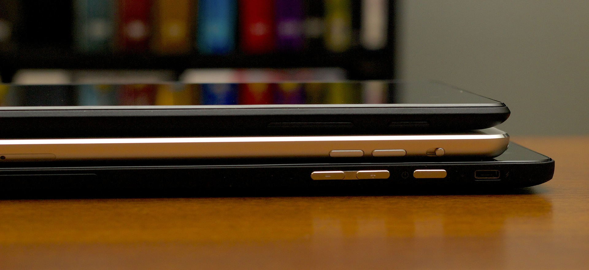 The Venue 8 Pro (bottom) is a little thicker than either the iPad or the Nexus 7. The micro USB charging port is just above the power button.