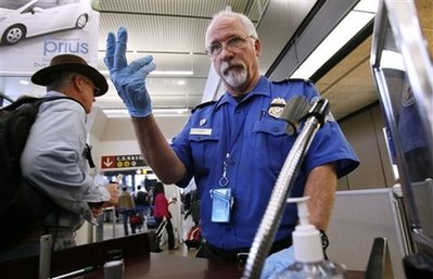 A TSA agent signals to a passenger at a security check point.