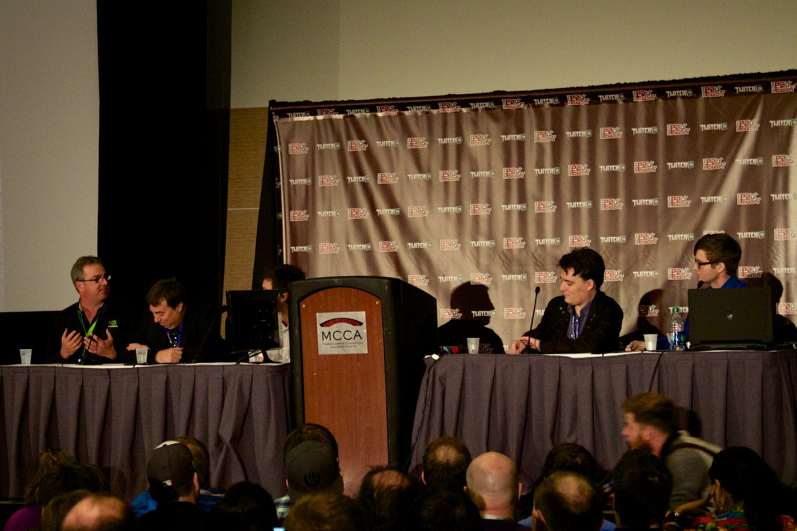 The panel, with Higby's face partially obscured by a monitor.