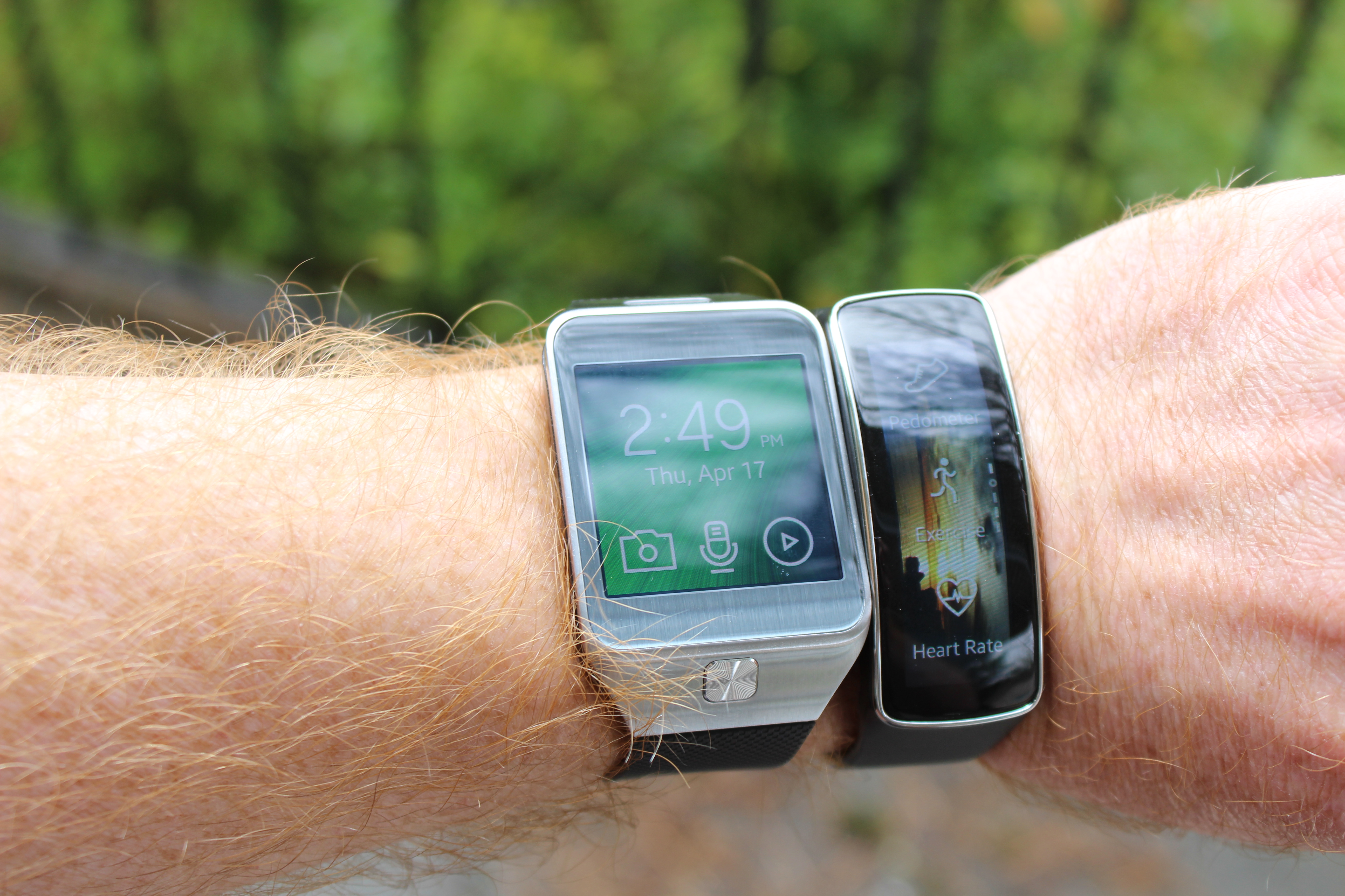 "The Gear 2 and Gear Fit in direct sunlight, set to ""outdoor"" brightness mode."