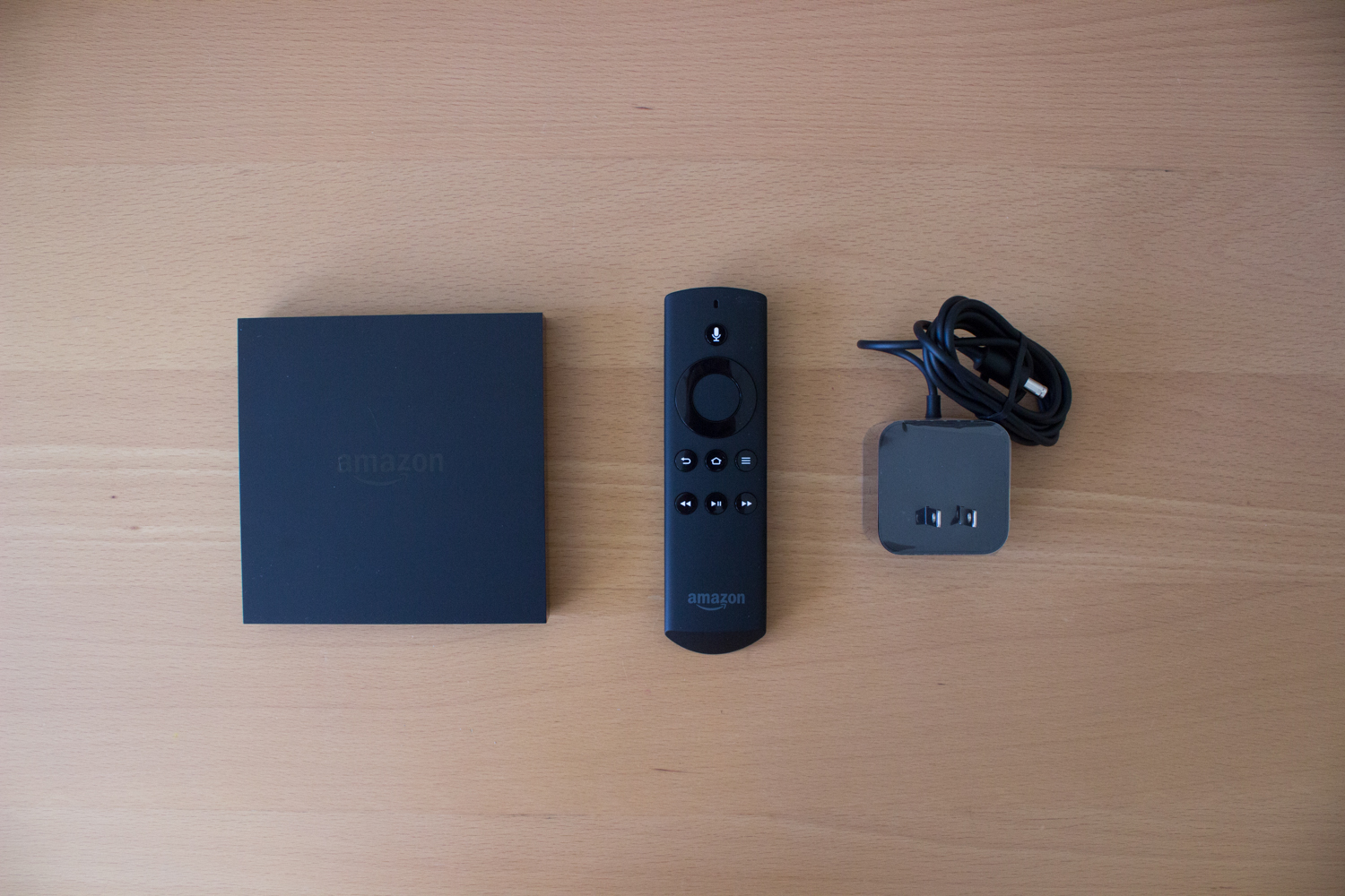 From left, the Fire TV box, the remote, and the power cable that come in the box.