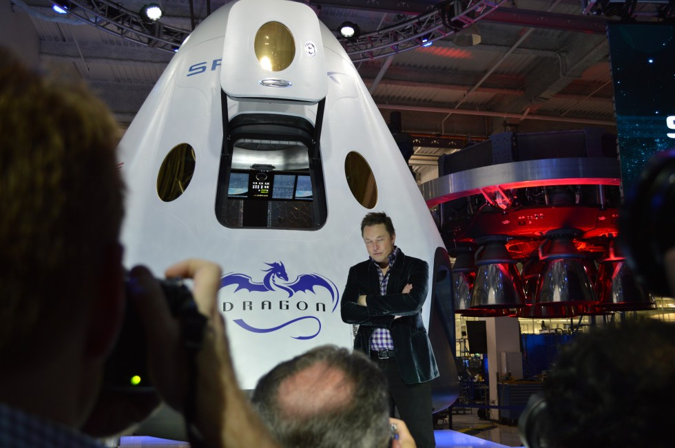 Elon Musk in front of the Dragon V2 with the touch screen control panel in the background.