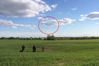 A photo from the Russian FSB, showing the drone flying as it was met by border guard officer.