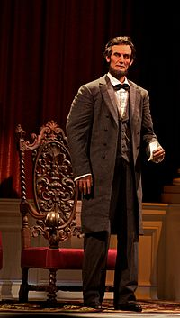 The animatronic president Lincoln standing to deliver his speech.