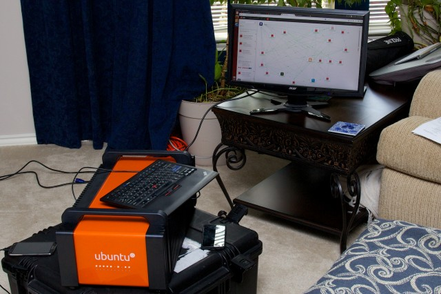 My very own cloud demo station! The Orange Box as it was shown to me in my living room, with the Juju console in the background showing an operational OpenStack deployment.