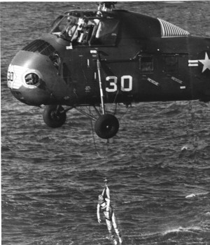 Grissom hanging from helicopter during his Mercury mission recovery. Grissom almost drowned when Liberty Bell 7's hatch unexpectedly blew outward after splashdown; the spacecraft sank. A subsequent investigation proved that the hatch's explosive bolts had ignited on accident, without input from Grissom.