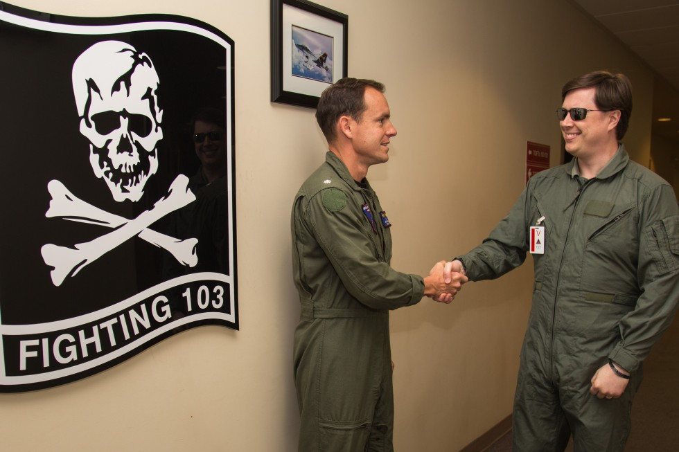 "Shaking hands with Commander Matt ""Sparky"" Smith next to the VFA-103 flag in the sim building."