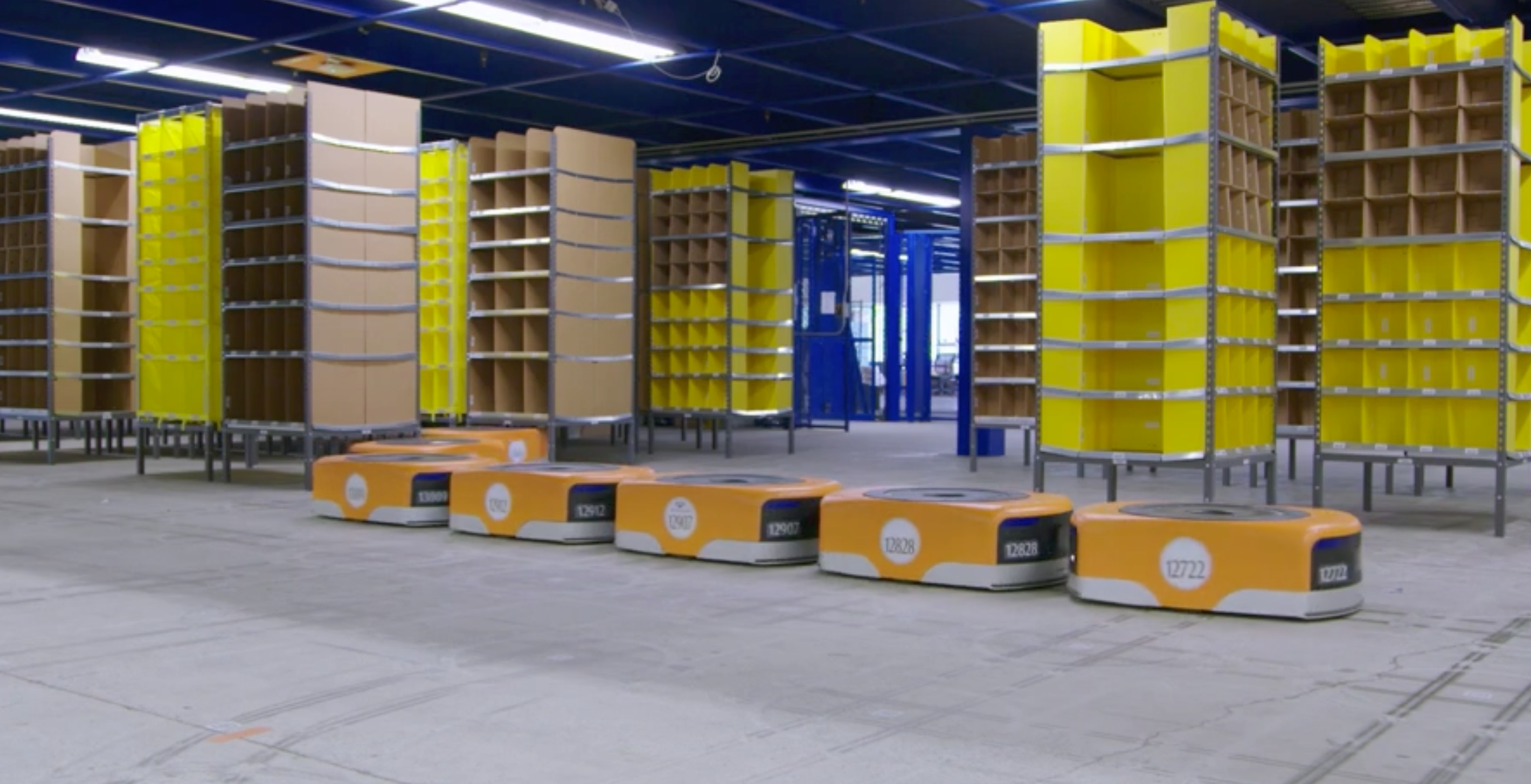 Short, squat robots drive around Amazon's fulfillment centers and pick up stacks that normally are full of products. Then, the robots take requested stacks to warehouse employees for packing purposes (in this photo, the stacks are empty).