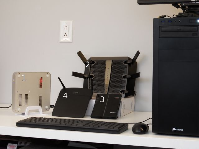 Clockwise from the far left: 1. the Ubuntu-powered Homebrew Special, 2. the Netgear Nighthawk X6, 3. the Buffalo WHR-G300N-v2, and 4. the Linksys N600 EA-2750. Far right, looming over them all: Monolith, one of the two servers used for testing.