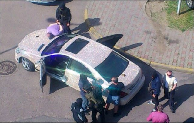 An alleged embezzler is arrested on the hood of his diamond-encrusted Mercedes.