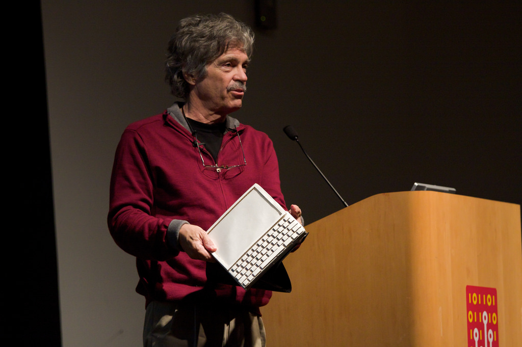 """Alan Kay with a mockup of the Dynabook. Although the Dynabook was proposed years before the necessary hardware was available, the ideas could be tried out on the Alto, an """"interim Dynabook""""."""