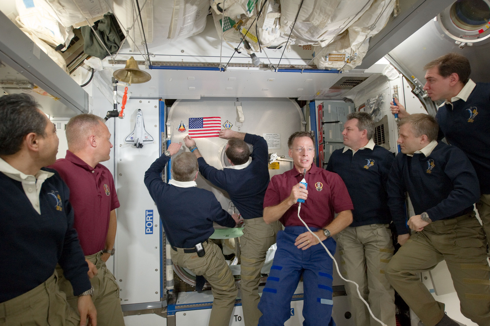 Mike Fossum and Ron Garan hang an American Flag on the station, during a ceremony, as Chris Ferguson says a few words.