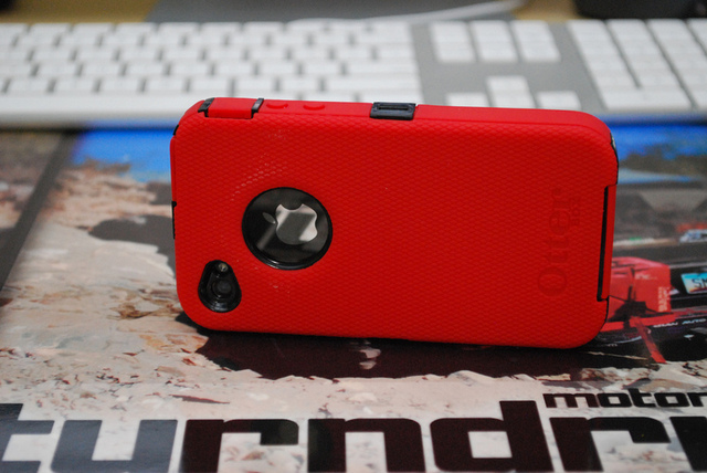 A colorful red Otterbox case in action, protecting the fragile iPhone within.