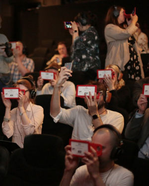 A bunch of journalists watching Bohemian Rhapsody on the Owl VR. That's me in the middle, taking a selfie. (Check out the Ars sticker covering the Apple logo. I'm so cool.)