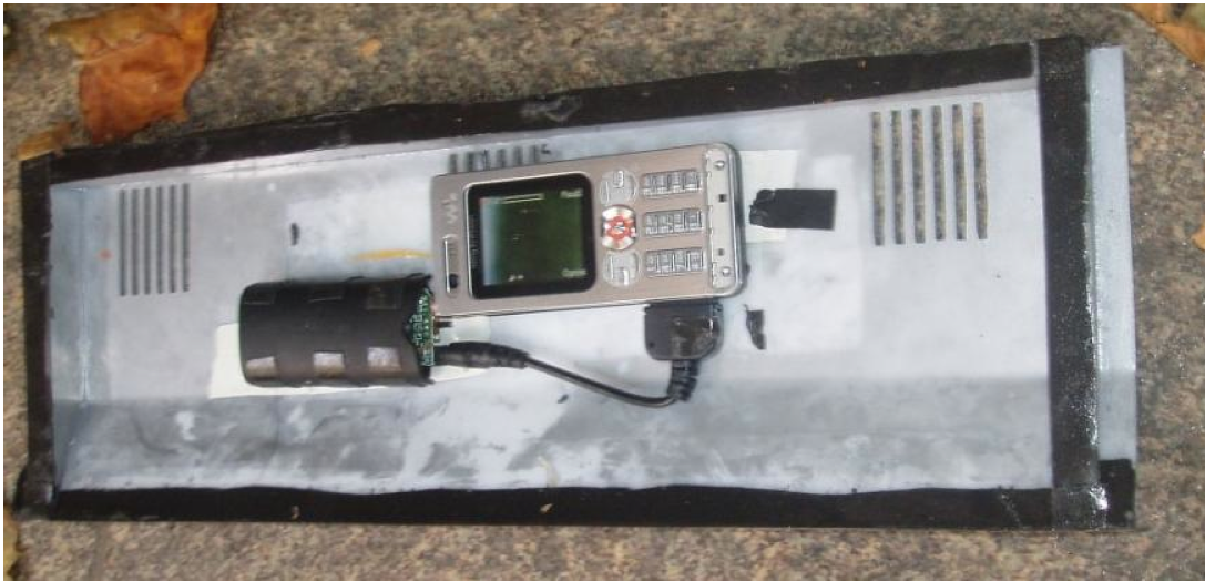 Two cellphones concealed in an ATM panel used to capture PIN and transmit the video wirelessly to a skimmer.