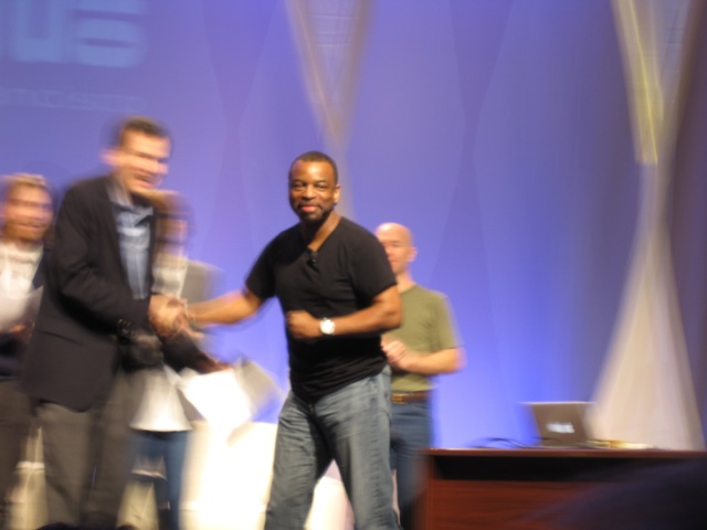 A blurry photo I took of Burton shaking Pogue's hand at the Macworld Expo in 2010, just after announcing that <em>Reading Rainbow</em> would be coming to the Internet