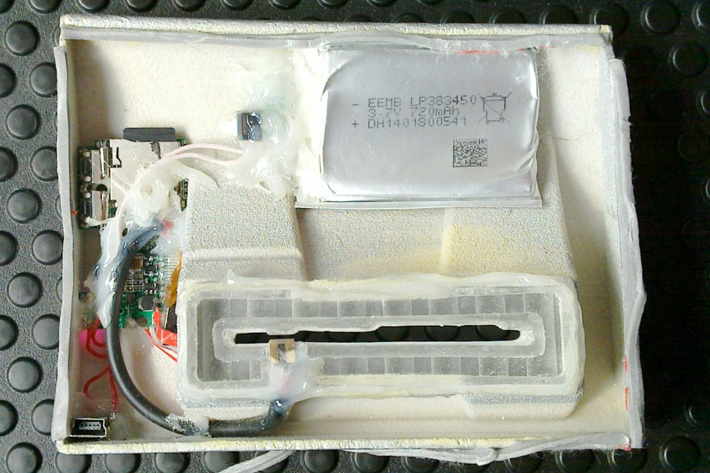 The back of the same skimming device, showing the battery, card reader, and storage device