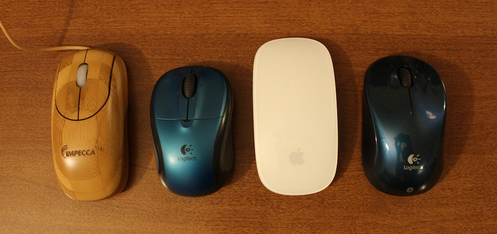 Impecca's wooden mouse, left, is about as long as a standard mouse, but is narrower than my Logitech travel mice and the Apple Magic Mouse.