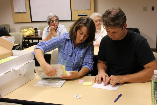 Temporary elections workers sifted through stacks of voted ballots to locate which ones needed to be audited.