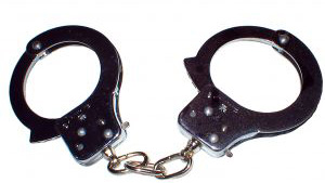 Stock photo of police handcuffs against white background.