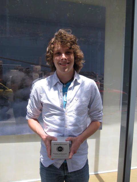 Logan Collins holding his Ars Design Award