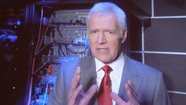 Alex Trebek exploring the depths of Watson's server racks during the IBM Challenge episode of Jeopardy.