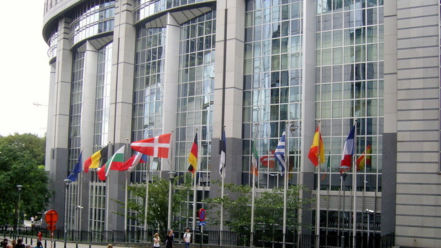 Exterior of the glass-and-concrete EU parliament building, ringed with flags.