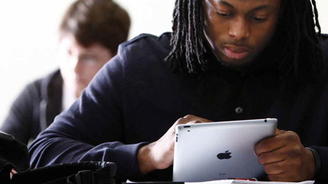 An ACU student uses an iPad in class, part of the school's