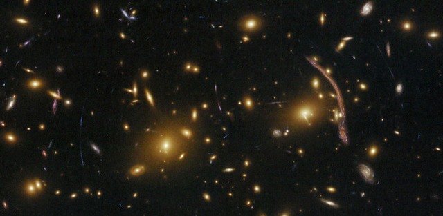 The red arc to the right of the image is caused by gravitational lensing.